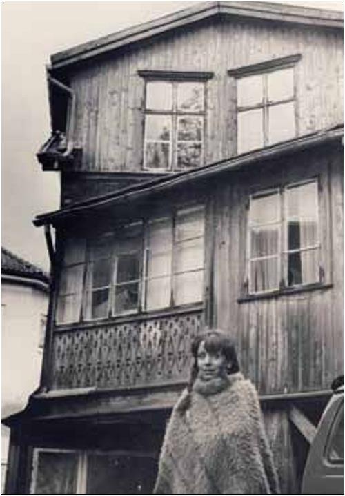 Eva Johansen fotografert på baksiden av huset etter kjøpet i 1982. Ved restaureringen ble utsmykningene nede til venstre kopiert og brukt på nytt under vinduene på begge sider av inngangen. (Foto: Grete Qvist Øystå, Akershus Amtstidende).