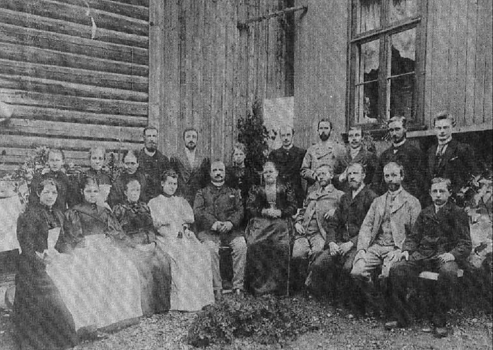 Martin Skancke og hans hustru (nr. 5 og 6 foran fra venstre) omgitt av familie og ansatte. Nr. 2 foran fra venstre er Bertha Hansen, gift Gulliksen. Nr. 3 er frøken Johnsen som senere overtok en manufakturforretning. Nr. 8 er bokholder og kasserer Reissiger. Nr. 10 er enten bror eller sønn av feiermester Nilsen. I bakre rekke fra venstre ser vi: Nr. 3 fru Paulsen i Tamburbakken. Nr. 6 Skanckes datter Fredrikke. Nr. 7 sønnen Birger som drev en moteforretning i Rangsætergården, hvor doktor Rangsæter senere holdt til. Nr. 8 het Amundsen. Han ble gift med Fredrikke Skancke. Ytterst til høyre i bakre rekke står Kristian Andresen.