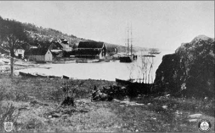 Båthavna 1895. Ishus og Jacob Carlsens sjøbod er dominerende i bukta, med lav  trehusbebyggelse bak. Strendene var lagerplass for tønner, bjelker og plank. (Bildebehandling: Joar Foto)