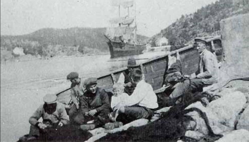 Fiskerlaget til Randin ved «Kastet» i Gylte bøter garn. Gylteholmen i bakgrunnen til venstre. Seilskuta har heist seilene opp til tørk.