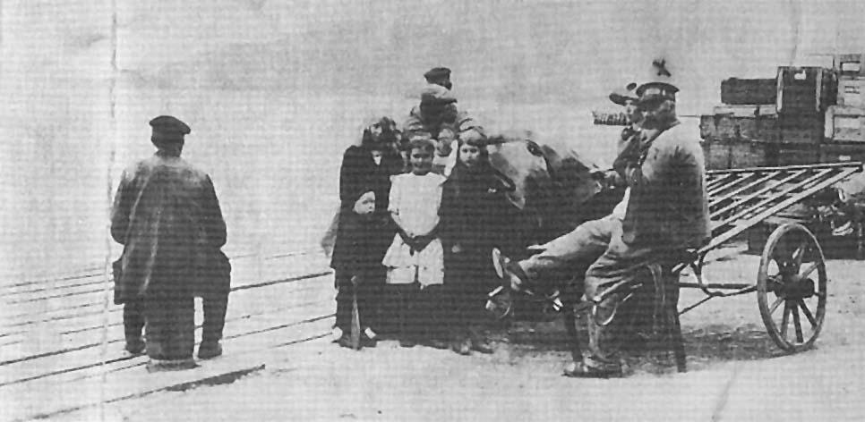 Lehmannsbrygga 1910. Bybud nr. I Larsen sitter på bryggepælen, bybud nr: 3 Andreassen sitter på drakjerra.