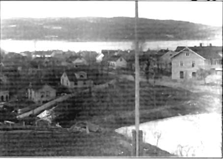 """Dette fotografiet er antakelig tatt like etter at Holmedammen ble anlagt som isdam i 1880. Er par år før var det blitt bygget en ny vei ned til Drøbak, fra Dyrløkke langs Ullerudtjernet, over bekken ved lensmann Næss og rundt den store bygningen vi ser til høyre på bildet (dette er Ruud gården som ble revet i 1981 etter lange stridigheter). Veien svingte 90 grader rundt huset og ble inntil nylig kalt """"Fardalhjørnet"""". Videre derfra ble veien kaldt Lindtruppen. I 1929 brast demningen under en flom og Raskebekken ble en elv for noen timer. Snekkermester Telles hus var ikke bygget da dette fotografiet ble tatt, derfor ser vi tydelig Gulliksbakken et stykke nedenfor demningen."""