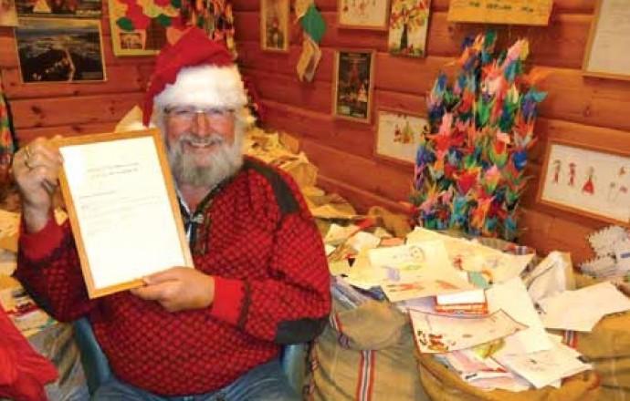 Drøbaks julenisse Tom Kristiansen med det kommunale vedtaket, det endelige beviset på at han er kommet hjem til Drøbak. (Foto: Torkil Baden).